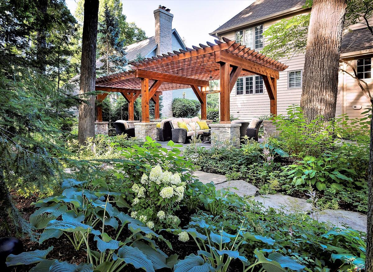 open air pergola with seating and surrounding landscaping