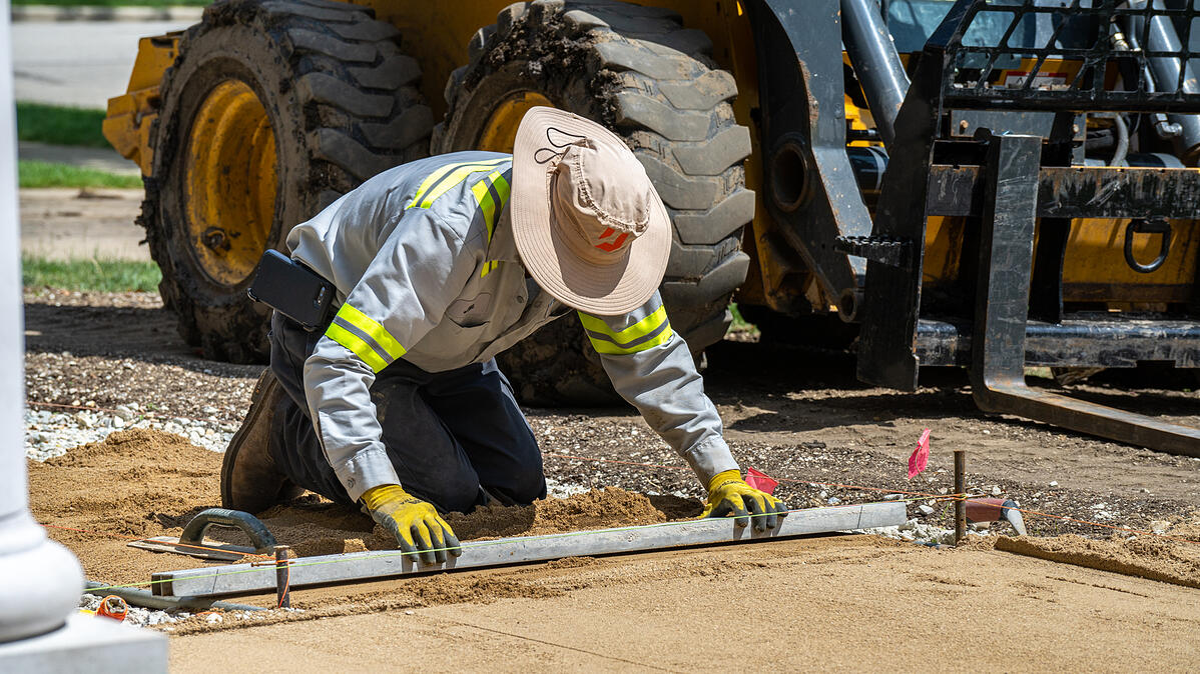 paver patio installation crew checks base for level ground