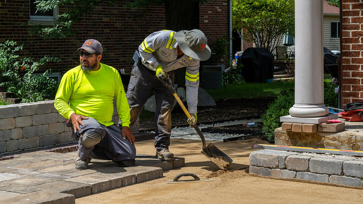 landscape installation team lays paver patio on solid base