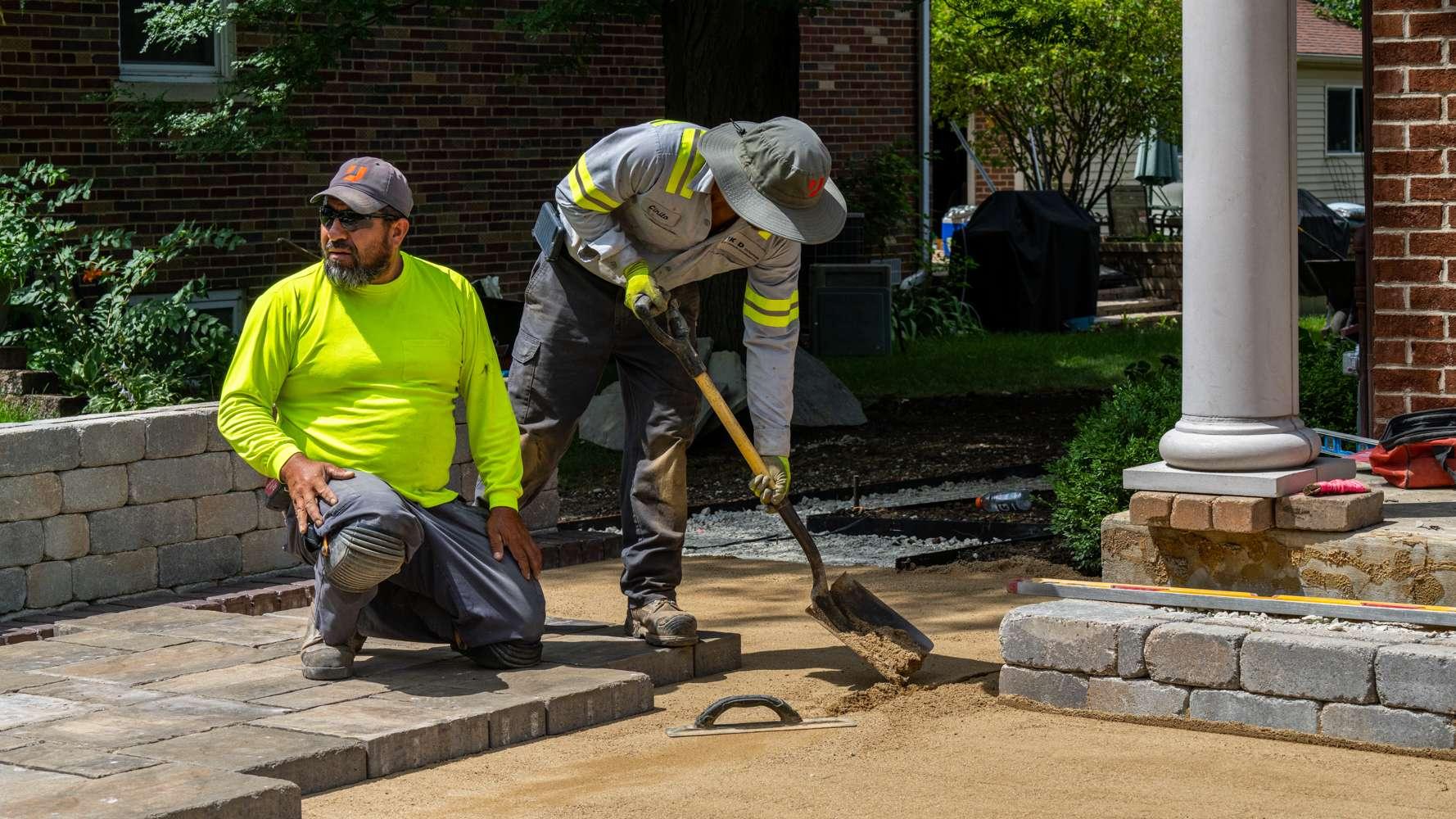 Landscape installation crew installing a paver patio