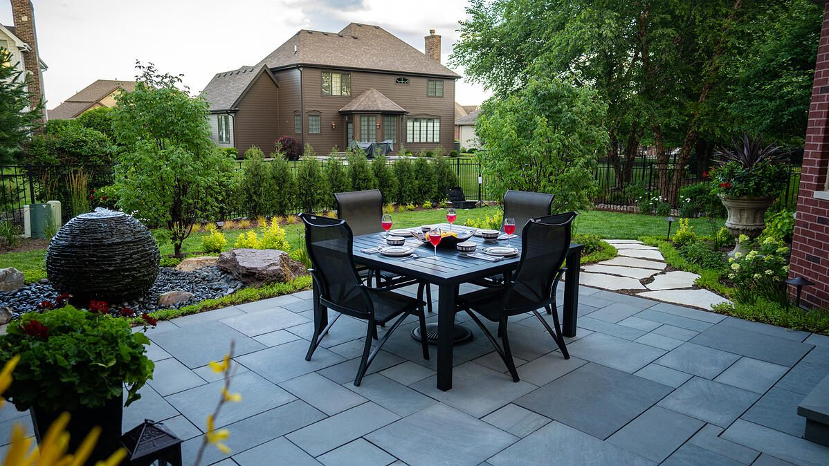 paver patio with area for dining and water feature